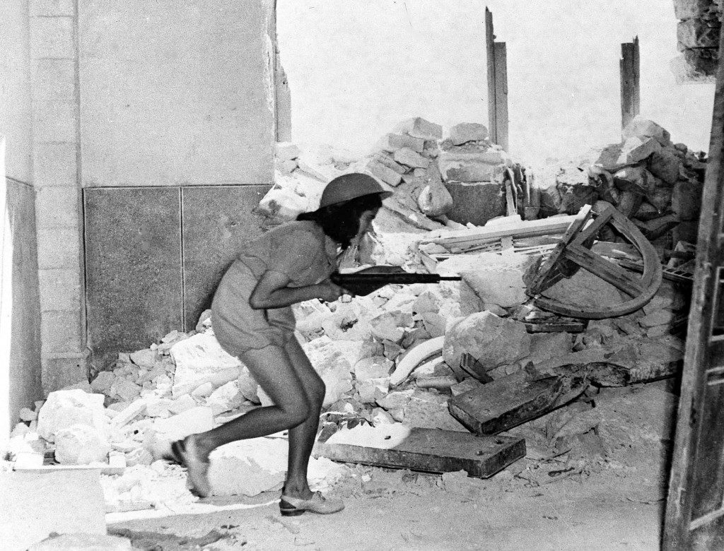 An Israeli soldier, armed with a sten gun, picks her way through the shattered walls of Sulimans Way, in the old city of Jerusalem, Palestine, July 20, 1948, which forms a front line between the Arabs inside and Jewish forces outside the walls. Fierce fighting happened between the two forces following the expiry of a two-day truce. (AP Photo/Pringle) Ref #: PA.5736824 Date: 20/07/1948