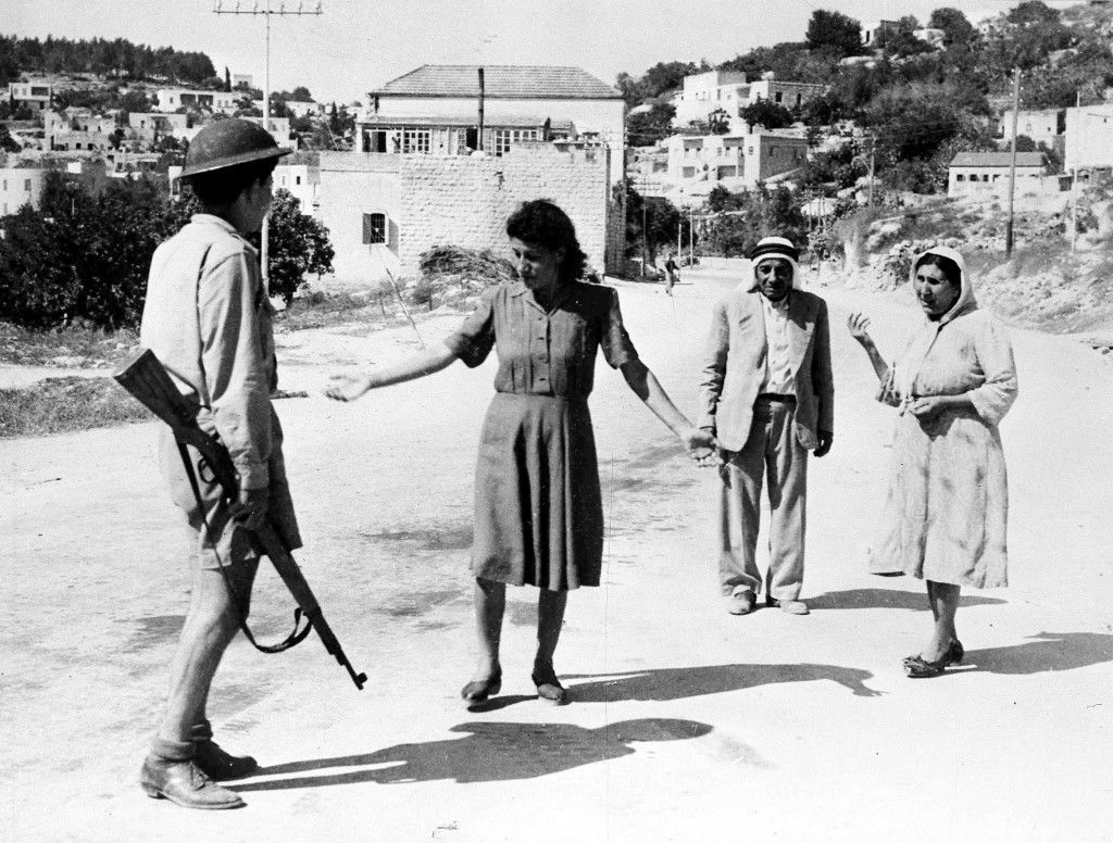 An Israeli soldier, armed with a rifle, stop some arabs in a street in Nazareth, Palestine, July 17, 1948, as they are travelling after the allotted curfew time. Israeli forces had occupied the town earlier that day. (AP Photo) Ref #: PA.5736836 Date: 17/07/1948