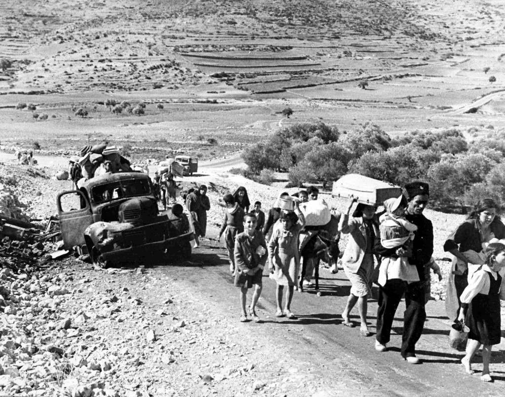 A group of struggling Arab refugees walk along the dusty road from Jerusalem to Lebanon, carrying their meagre belongings with them, Nov. 9, 1948. The arabs have been driven from their homes by Jewish attacks in Galilee. (AP Photo/Pringle) Ref #: PA.5737111 Date: 09/11/1948