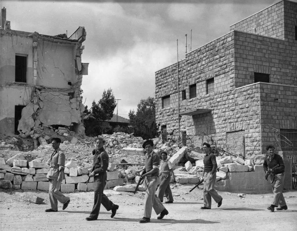 Jewish Haganah troops are seen on ppatrol near the no-man's-land line in Katamon, a suburb of Jerusalem, Palestine May 6, 1948. In the back left is the Arab owned hotel Semiramis, by bombed by Haganah forces four month ago, with the argument that it was used as an Arab headquarter for commanders of the fighting Arabs. 15 men and women were killed in the explosion. Katamon, once an Arab stronghold, was wrested from them by the Haganah forces in a three day battle ending May 4, 1948. There was a continuous battle with automatic weapons and armoured cars. Except for the Haganah gurds and patrols all the former residents have departed. (AP Photo/Pringle) Ref #: PA.5737133 Date: 06/05/1948