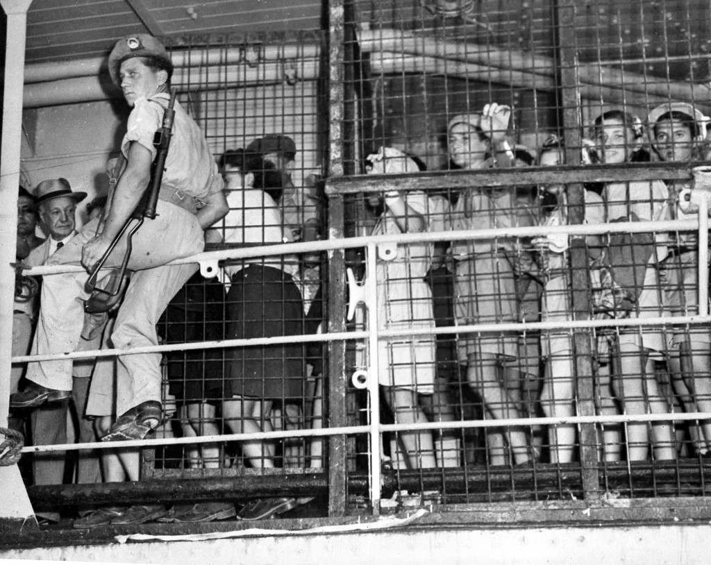 British soldier, armed with a sten gun, on guard near the cages of orphaned Jewish children, as they prepare to leave a ship to live in Haifa, Palestine, Aug. 21, 1947. Five hundred orphans, the majority of whom lost their parents during World War II, were interned in Cyprus and brought to Palestine as part of the monthly immigation quota. (AP Photo/Pringle) Ref #: PA.5737162 Date: 21/08/1947
