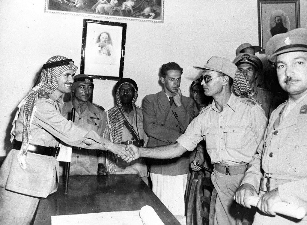 Commander of Israel's Jerusalem Brigade, Colonel Moshe Dayan, right, and Arab Legion Commander Abdullah Bey El-Tel, shake hands after a conference in a monastry in Jerusalem's no-man's land, Aug 22, 1948. Facing camera right, is Lieutenant Colonel Ahmed Abd Aziz, commander of the Egyptian forces in the southern section of Jerusalem. A few hours after this picture was taken Colonel Aziz was ambushed and killed. (AP Photo/Pringle) Ref #: PA.5737197 Date: 22/08/1948