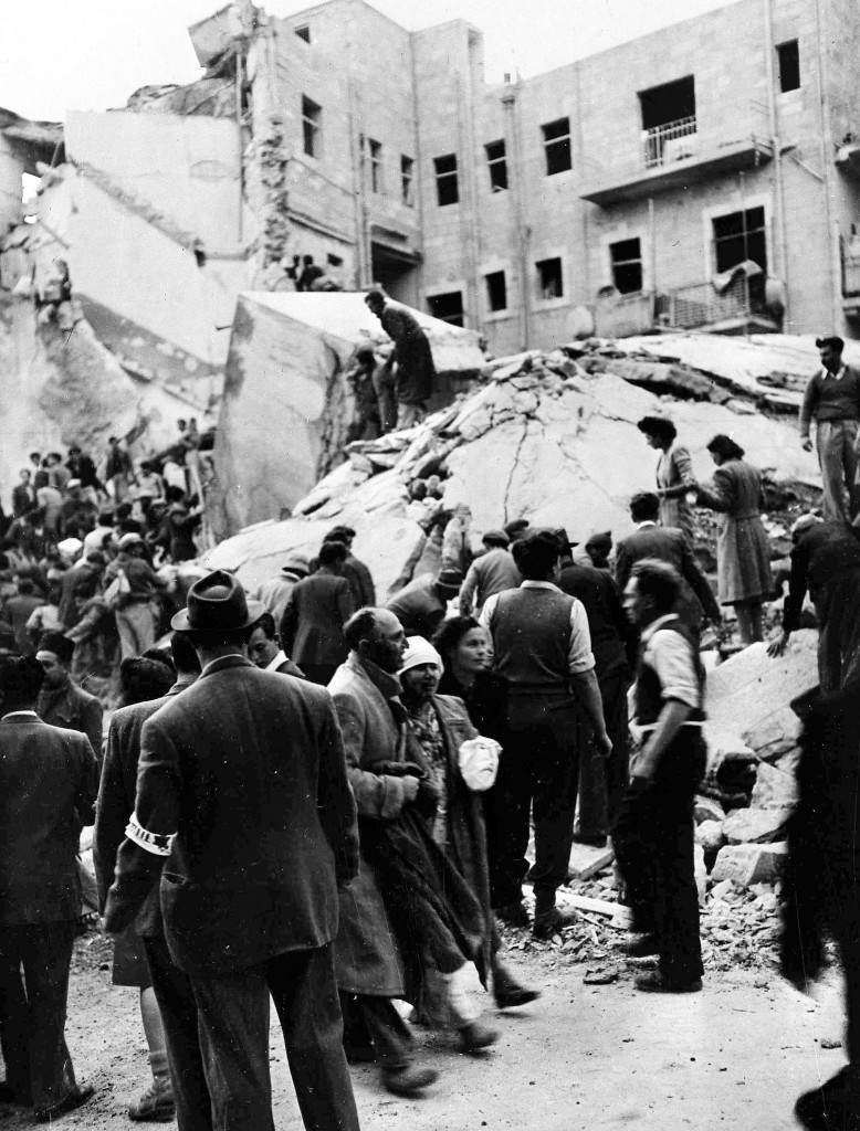 An injured Jewish couple walk past rescuers searching for wounded and dead people in the wreckage of shops on Ben Yehuda Street, Jerusalem, Feb. 22, 1948, after a bomb exploded. The bomb killed 52 Jews and wounded 100 more and levelled buildings on both sides of the street. (AP Photo/Pringle). Ref #: PA.5737217 Date: 22/02/1948