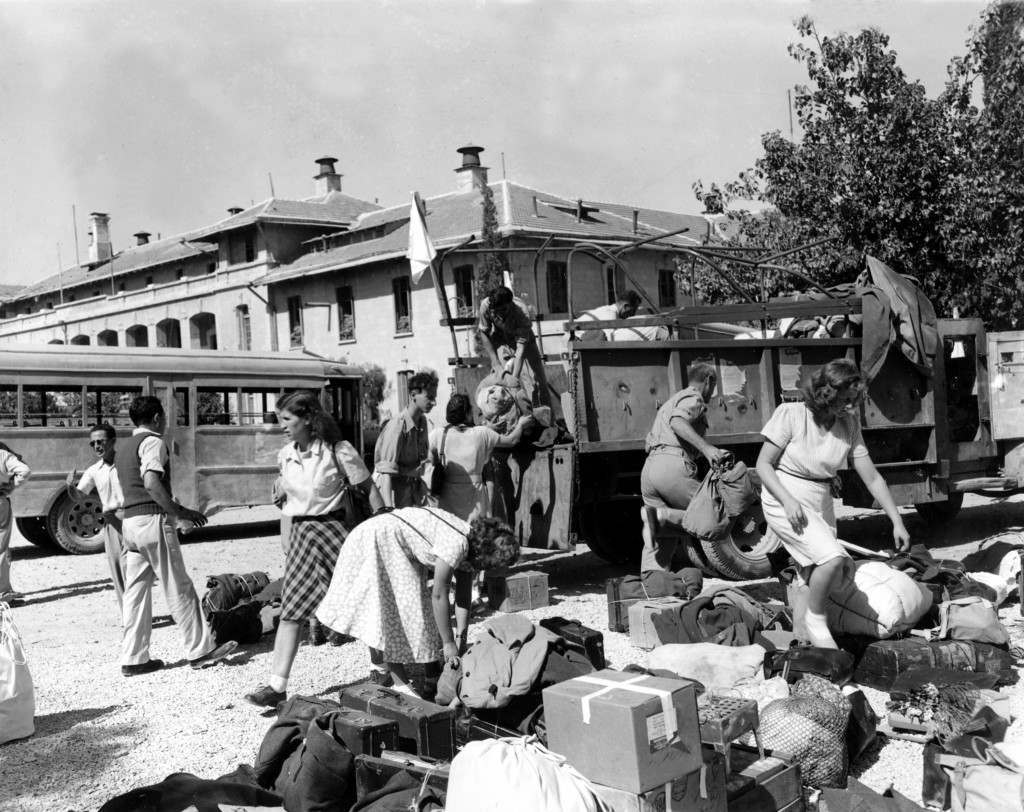 Jewish nurses stranded for three months in the neutral area on Mount Scopus, which is in Arab-held territory, sort out their luggage after being brought back safely to Jerusalem in armored buses of a United Nations convoy on Oct. 8, 1948 in the Arab-Israeli War. Israeli police, also stranded in the demilitarized zone, were brought back with them and the Arabs permitted police replacements to go to Mount Scopus. (AP Photo/James Pringle) Ref #: PA.5737255 Date: 08/10/1948