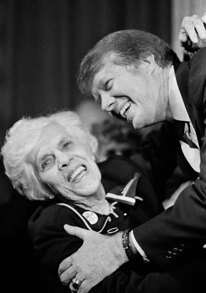 """Georgia Gov. Jimmy Carter gets a hug and a kiss from his mother, Lillian Carter,in Atlanta Dec. 12, 1974. Carter often sent his mother to meet with foreign dignitaries and attend state funerals, but it wasn't until he started researching a new book about her life that he learned just what the woman known as """"Miss Lillian"""" did on those visits. (AP Photo/Joe Holloway Jr.) Ref #: PA.5932751  Date: 12/12/1974"""
