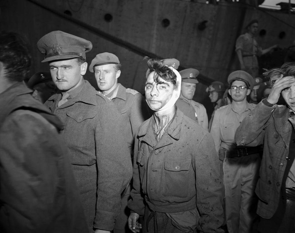 A young Jewish boy, wounded and bloody after the fight with British soldiers on board the refugee ship Knesset Israel, passes a line of soldiers to board the troopship Empire Heywood on Dec. 4, 1946 in Haifa, one of three vessels on which passengers from the refugee ship were deported. (AP Photo) Ref #: PA.7090686 Date: 04/12/1946