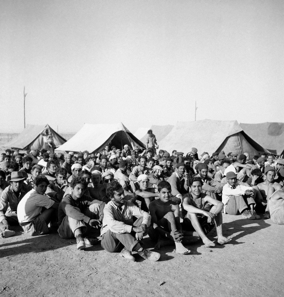 Joshua Cohen, 12, one of nearly 300 prisoners taken by Trans-Jordan Legion on surrender of Old City Jewish quarter, Jerusalem, 28/5 and now held in Trans-Jordan. He is seated on the ground with other prisoners for sunset check by Legion guards on June 4, 1948 in Trans-Jordan. (AP Photo/ Daniel De Luce ) Ref #: PA.7091311 Date: 04/06/1948