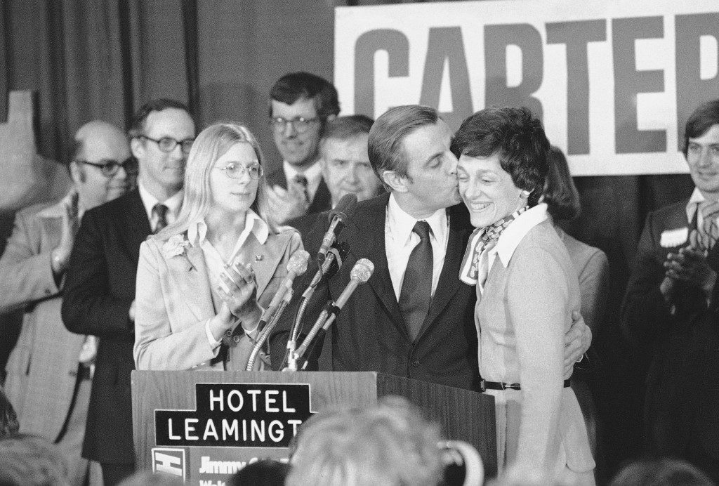 Vice President elect Walter Mondale gives his wife Joan thank you kiss for her efforts during his campaign as Mondale and his family appeared before wellwishers at the Leamington Hotel, Nov. 3, 1976. At left is daughter Eleanor. (AP Photo/Jim Mone) Ref #: PA.7135259  Date: 03/11/1976