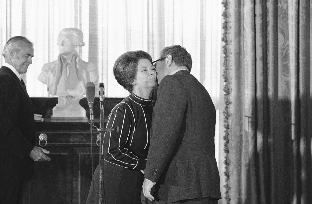 Secretary of State Henry Kissinger gets a kiss from Shirley Temple Black of Santa Monica, Calif., after Mrs. Black was sworn in as the new U.S. Ambassador to Ghana at a State Department ceremony in Washington on Friday, Sept. 20, 1974. (AP Photo/ Charles Harrity) Ref #: PA.7144594  Date: 20/09/1974