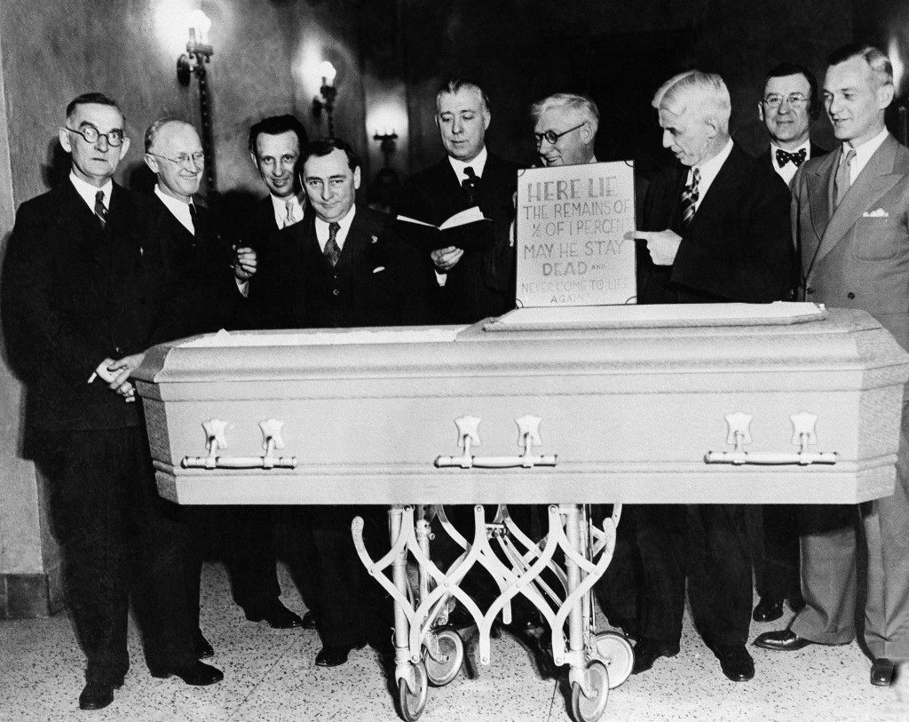 "Here is the ceremony employed by the Eagles club of Milwaukee to mark the passing of œ of one percent beer in favor of the 3.2 brew. At the stroke of the Eagles pictured at night on April 6, 1933, held up their drinking to give near beer a ""Decent"" funeral. The sign over the coffin reads: ""here lie the remains of œ of 1 percent. May he stay dead and never come to life again. (AP Photo) Ref #: PA.7253520  Date: 06/04/1933"