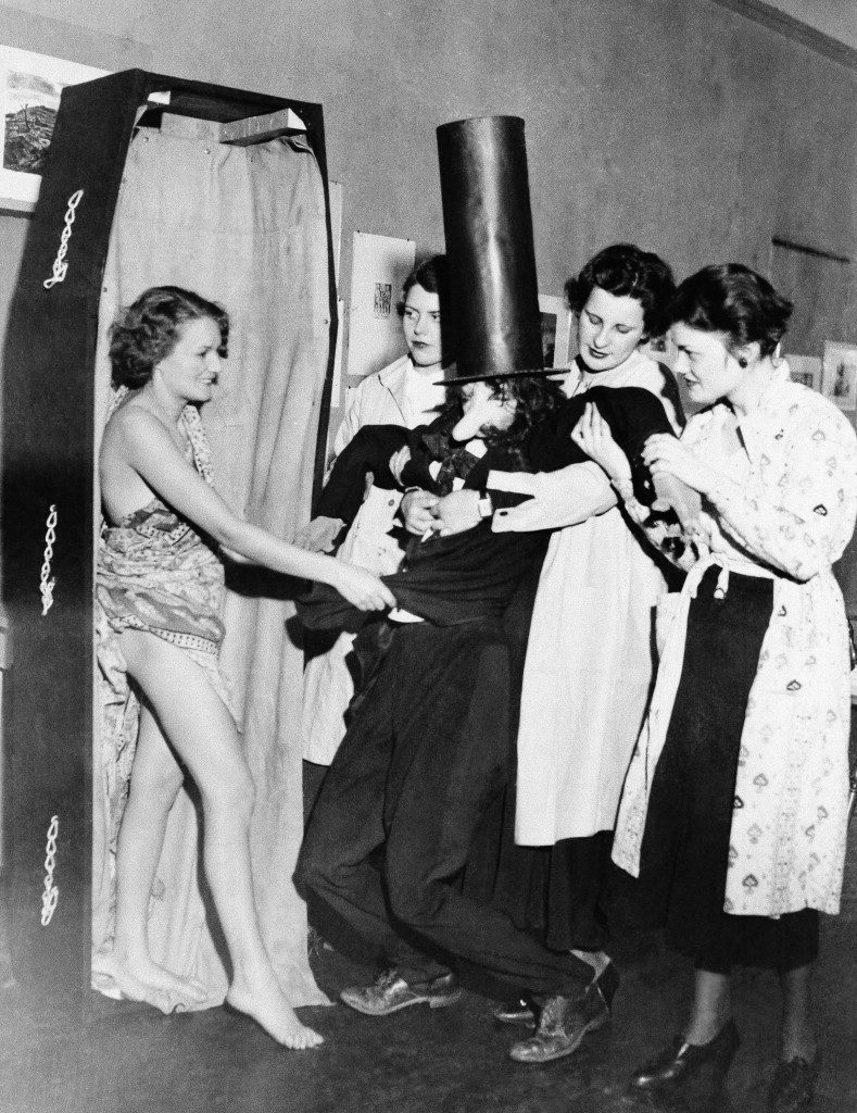 "Miss Bunny Swanson (left) impersonating the Spirit of Repeal, assisting happy art student ""Mourners"" in stowing away an effigy of prohibition during a ceremony at the Art Students League Building in New York on Dec. 4, 1933, a processional trip along Fifth Avenue, will follow, when the ""Remains"" will be escorted to the ballroom of a New York Hotel, to lie in state during the league repeal ball and Revel on December 5. (AP Photo) Ref #: PA.7253564 Date: 04/12/1933"