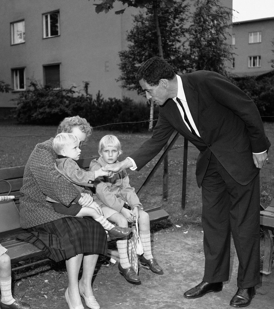 Sen. Claiborne Pell (D-Rhode Island) talks with a mother and two children, all three newly arrived refugees from communist East Germany. The conversation took place during Pell's visit on July 22, 1961 of West Berlin's largest refugee center, Marienfelde. (AP Photo/Reichert) Ref #: PA.7278691  Date: 22/07/1961