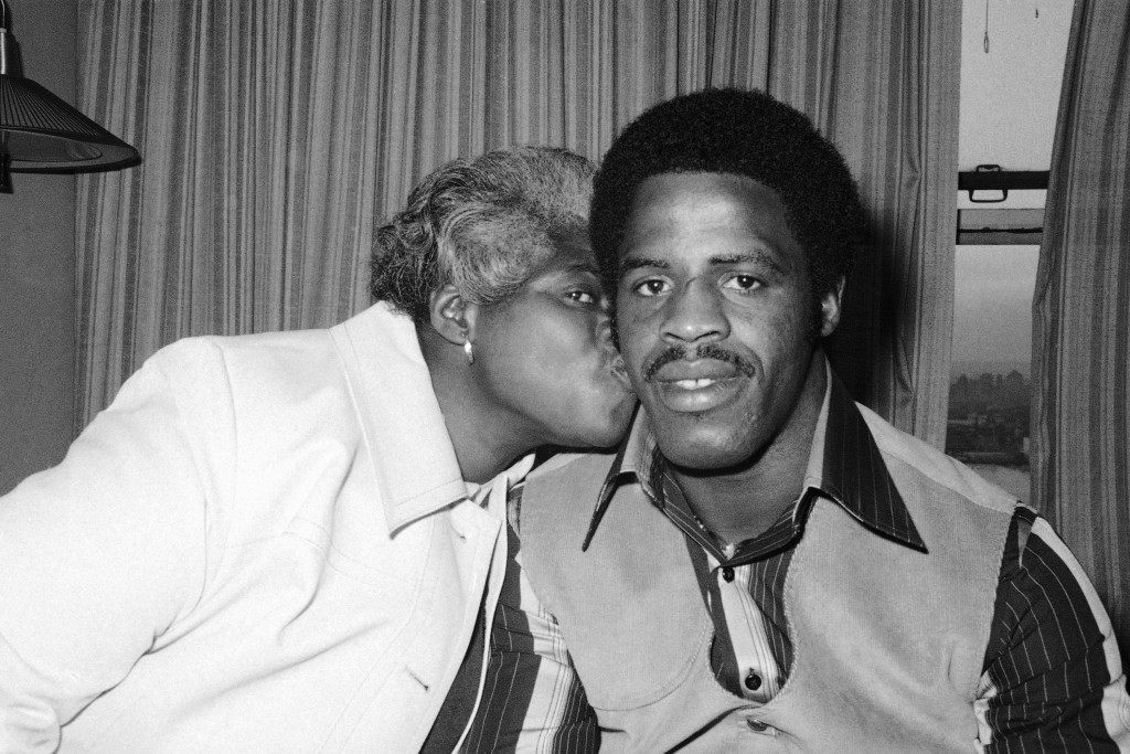 "Earl Campbell's mother, Ann, plants a kiss on cheek of her son as the Texas football star waits in his New York hotel room to attend the Heisman trophy award dinner, Thursday Dec. 8, 1977. Campbell, who is going on to pro football as a certain first round draft choice, says he'll take part of his pro money and buy a house for his mother who raises roses for a living. A widow, who has raised 11 children, Mrs. Campbell says she tried to discourage earl, ""but he always loved football."" (AP Photo) Ref #: PA.7333673  Date: 08/12/1977"