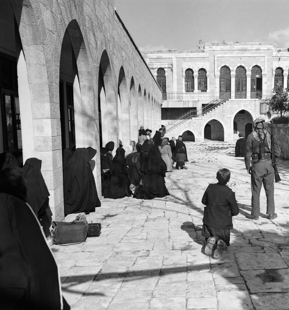 While an armed Arab (right) stands guard, Christian Pilgrims kneel in what is said to have been the court of Pontius Pilate in Jerusalem, scene of first station of the way of cross. The place where Pilate condemned Jesus to death had been a British Police Station but recently was abandoned because of Arab-Jewish strife. Now it is used as headquarters of Arab National Police, Friday, March 26, 1948 in Jerusalem observances of stations of cross which were repeated, March 26, Good Friday. (AP Photo) Ref #: PA.7380227 Date: 26/03/1948