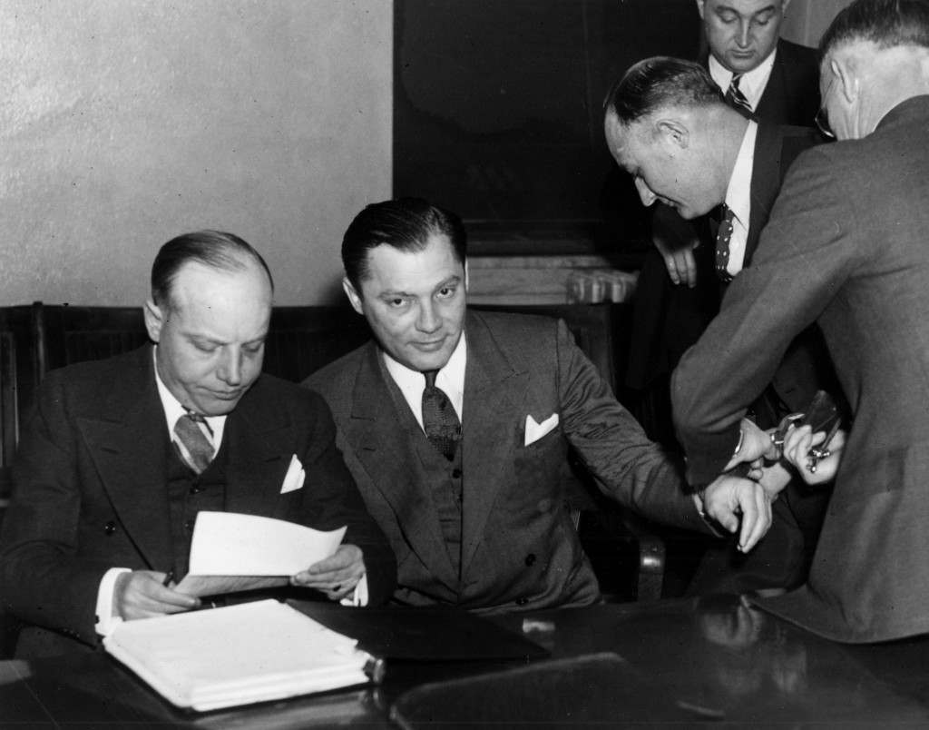 "Isadore ""Kid Cann"" Blumenfeld, center, charged with the murder of Walter Liggett, Minneapolis weekly newspaper publisher, has his manacles removed in court on the first day of his trial in Minneapolis, Jan. 20, 1936. At left is Thomas McMeekin of St. Paul, defense counsel. (AP Photo) Ref #: PA.7428100  Date: 20/01/1936"