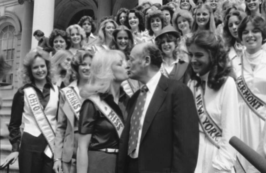 Kim Tomes, from Texas, the reigning Miss U.S.A., gives New York Edward Koch a kiss as he greets 51 Miss U.S.A. contestants on the steps of New York's City Hall, Thursday, April 13, 1978 at right is Miss New York, Darlene Cara Javits, of Plainview. The beauty queens are in New York on a visit, and a New Miss U.S.A. will be selected in Charleston, S.C. on April 29. (AP Photo/Pickoff) Ref #: PA.7430225  Date: 13/04/1978