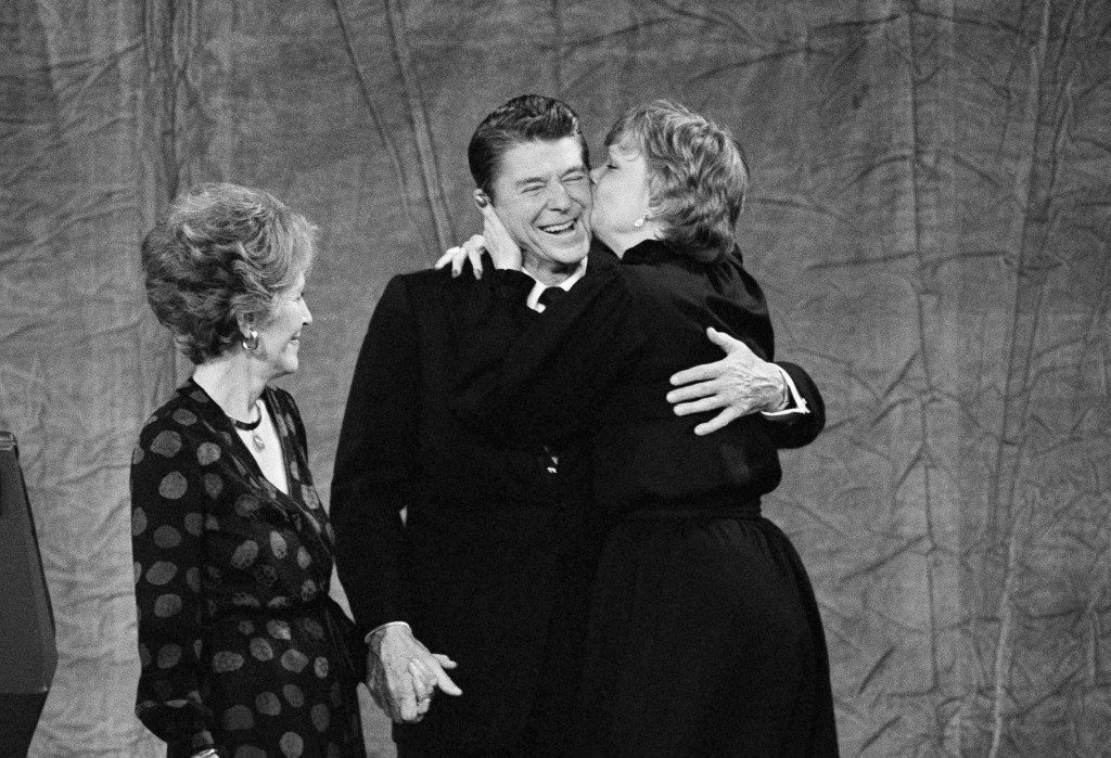 Maureen Reagan, right, gives a kiss to her father, president-elect Ronald Reagan, while Nancy Reagan looks on, Nov. 5, 1980. Reagan shared center stage with his family at Century Plaza Hotel in Los Angeles after defeating President Jimmy Carter in the presidential election. (AP Photo) Ref #: PA.7520115  Date: 05/11/1980