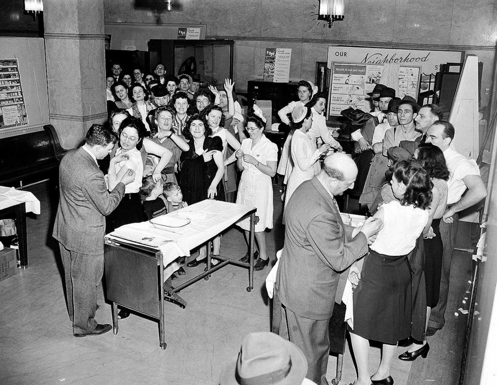 Dr. Walter X. Lehmann, left, and Dr. Kurt L. Brunsfeld, right, vaccinate two unidentifed women for smallpox April 14,1947, as others await their turn in New York City Health Department building. Crowds turned out after Health Commissioner Israel Weinstein's radio plea that the public be vaccinated. His plea came after nine cases, incuding two fatalities, were reported. (AP Photo/Tony Camerano) Ref #: PA.7523885 Date: 14/04/1947