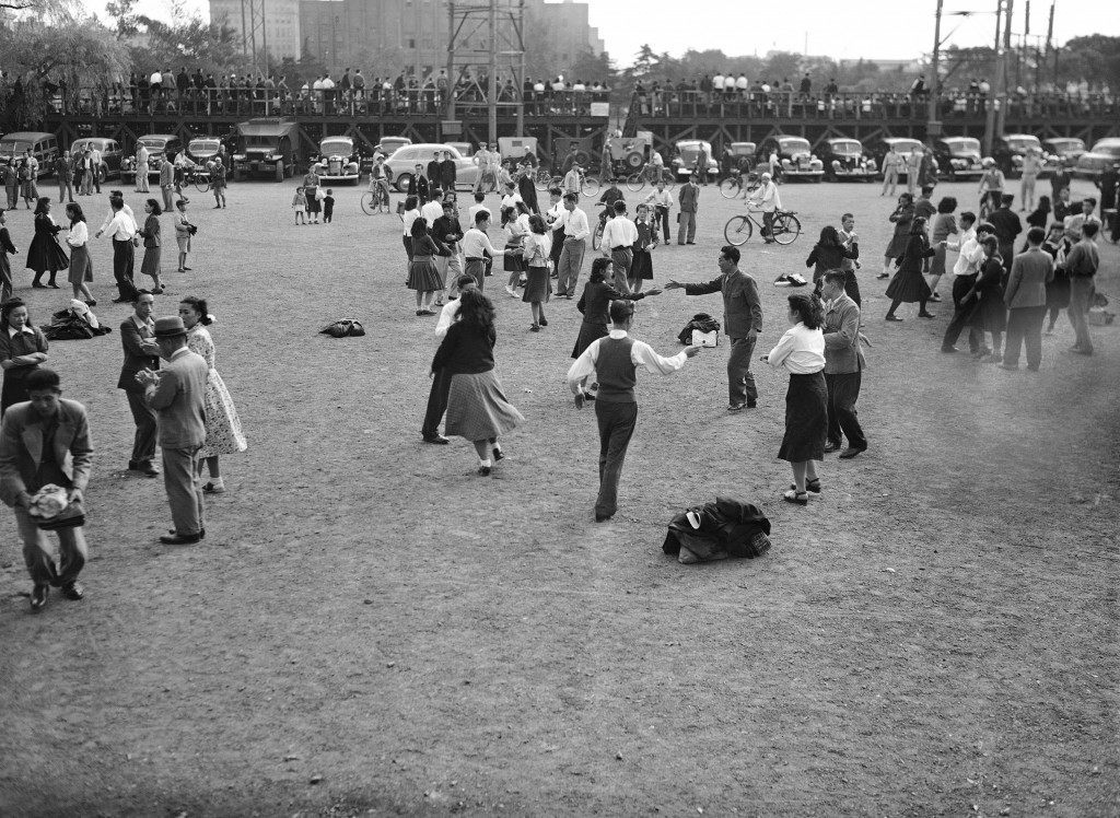 "The Virginia reel, a favorite American folk dance, is something new for the Japanese, dancing in Hibiya Park, Tokyo, Oct. 18, 1949. The music is ""Parlez Vous,"" a World War I tune. The dancers are employees and friends of a Tokyo business organization, which got the people out for square dancing on a balmy day as part of a new move to better employer-employee relations. (AP Photo/Charles Gorry) Ref #: PA.7641882"