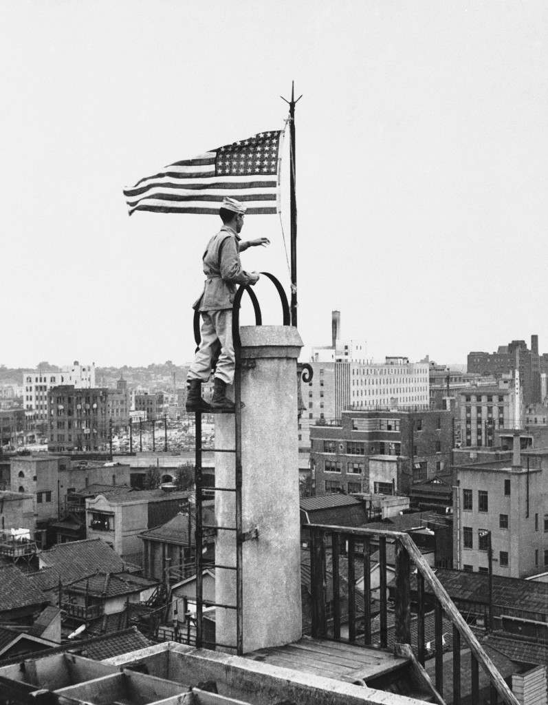 The American flag, first to fly over Tokyo since the Japanese surrender, is raised over the Nippon News building in downtown Tokyo on Sept. 5, 1945 by Lt. Bud Stapleton of Syracuse, N.Y. Photo radioed from Manila. (AP Photo) Ref #: PA.7642782