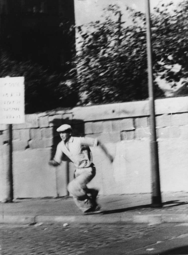 This Oct. 16, 1961 file photo shows a refugee from the German Democratic Republic (DDR) during his attempt to escape from the East German part of Berlin to West Berlin by climbing over the Berlin Wall. (AP Photo/File) PA-7923794