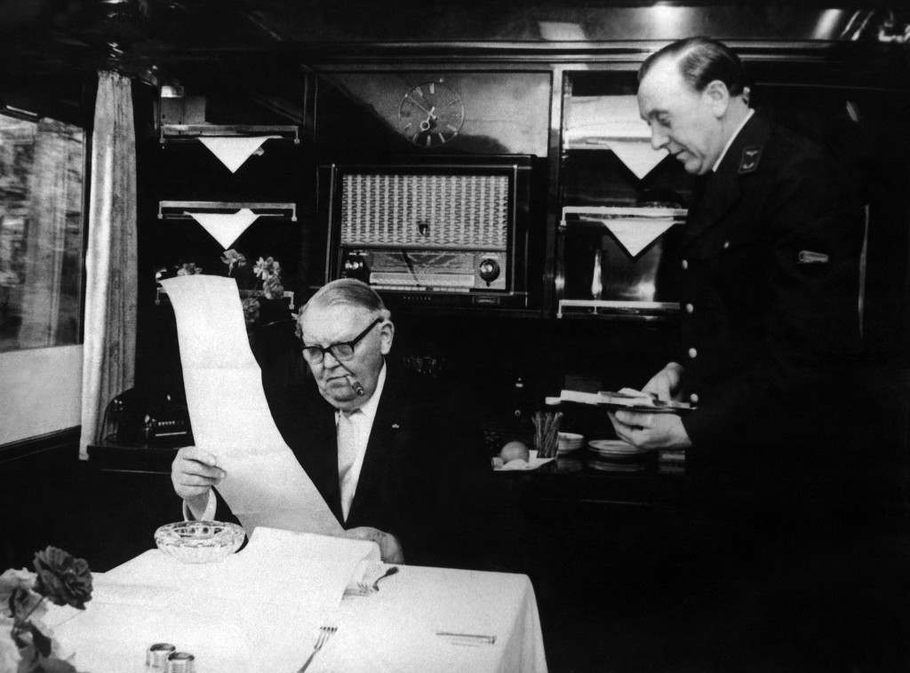 West German Chancellor Ludwig Erhard, reading and smoking in his office on his election campaign train on September 5, 1965, with a steward. (AP Photo) Ref #: PA.8243287  Date: 05/09/1965