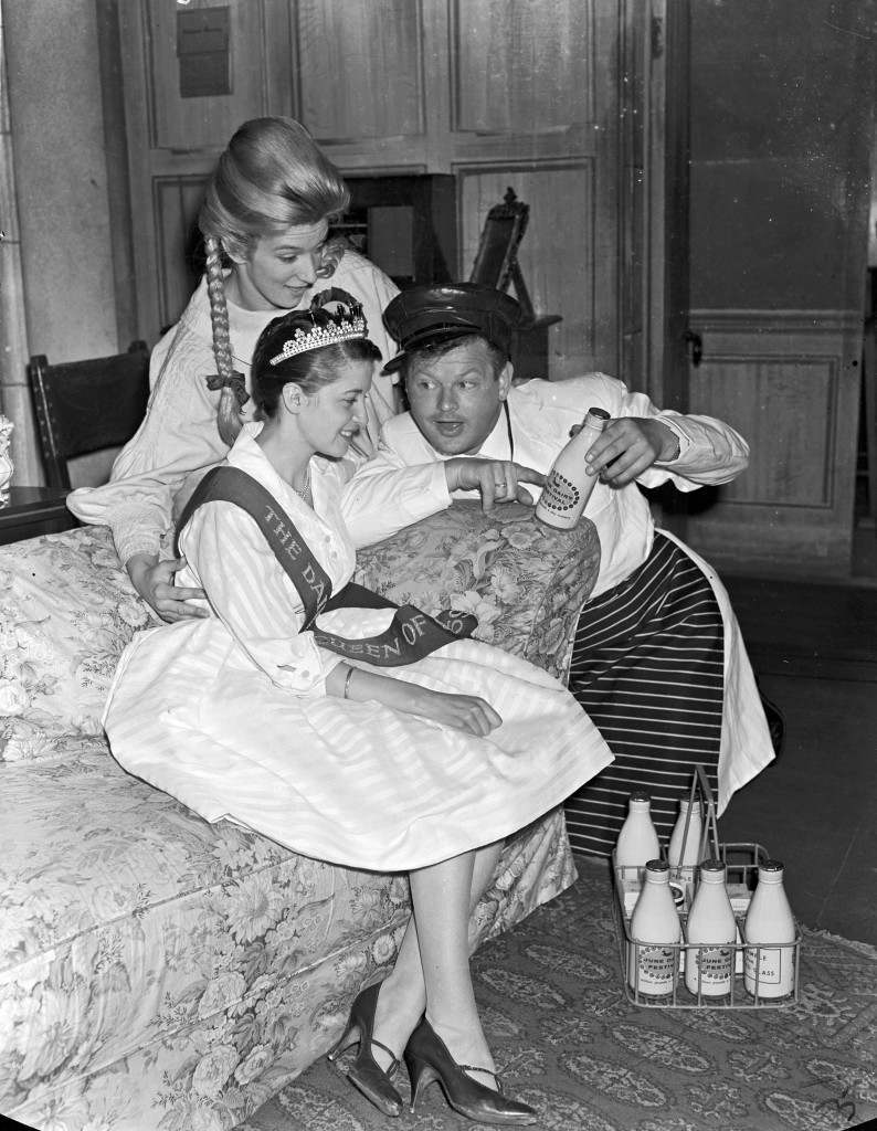 Majorie Watson, The Dairy Queen of 1959, of Goole, Yorkshire, is offered milk and cream by 'milkman' Benny Hill, during a press party to unveil the plans for Britain's June Dairy Festival at the Ambassadors Theatre, London. Seated behind her is The English Cheese Maiden, 20 year old Marylyn Hardy of Leeds.  Ref #: PA.8519703  Date: 18/05/1960