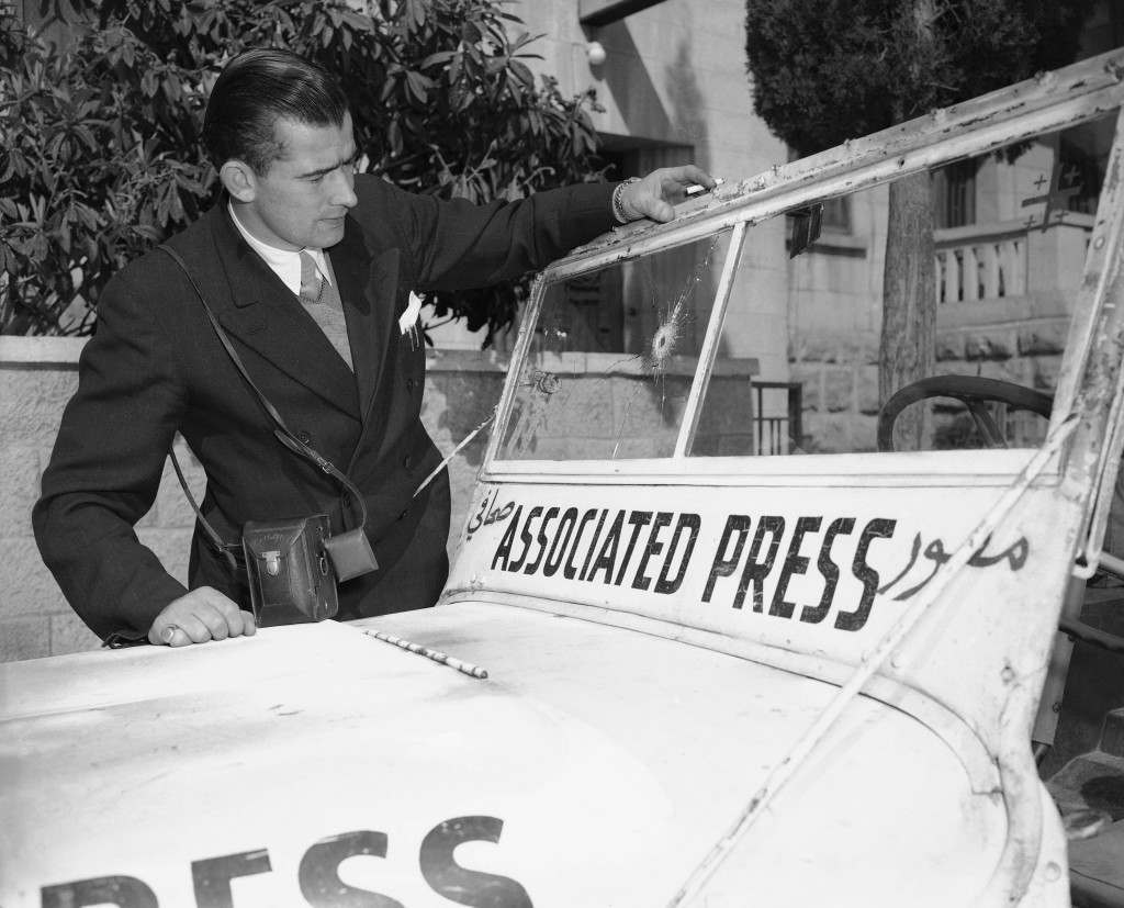Jim Pringle, Jerusalem staffer, looks at hole in windscreen of Associated Press jeep, Feb. 23, 1948, caused by Arab bullet during fighting with Jews in the Montefiore quarter. Pringle was just getting into jeep when bullet came through. (AP Photo) Ref #: PA.8591419 Date: 23/02/1948