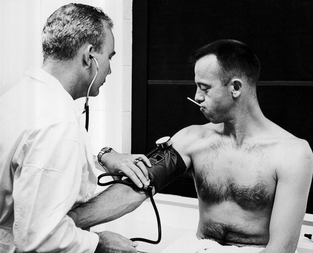 A thermometer in his mouth, Alan B. Shepard, Jr., watches as the astronauts? personal physician, Lt. Col. William K. Douglas, checks his blood pressure in Cape Canaveral, May 5, 1961. Shepard and his backup pilot, John H. Glenn, Jr., were given final physical examinations this morning at Cape Canaveral before Shepard took off on America?s first manned space flight. (AP Photo) Ref #: PA.8611817  Date: 05/05/1961