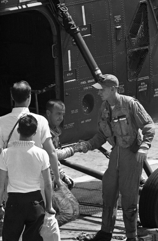 Carrier Lake Champlain crew member shakes hand of Alan B. Shepard, Jr., alighting from helicopter aboard the carrier after his space flight from Cape Canaveral, Fla., May 5, 1961. Shepard was picked up at sea by the helicopter and taken to the carrier. (AP Photo) Ref #: PA.8611828