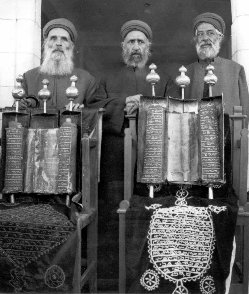 Samaritan High Priest Amran Ishak, center, and two unidentified Samaritan priests stand behind their scrolls of the Torah, or first five books of the Bible, on May 29, 1960. The Samaritans say the scroll on the right is 3,625 years old, written only 30 years after the death of Moses. These scrolls are handwritten in the primitive Hebrew alphabet. The Samaritan community live around their ancient temple site of Mount Gerizim in Nablus, Jordan. (AP Photo/Harry Koundakjian)