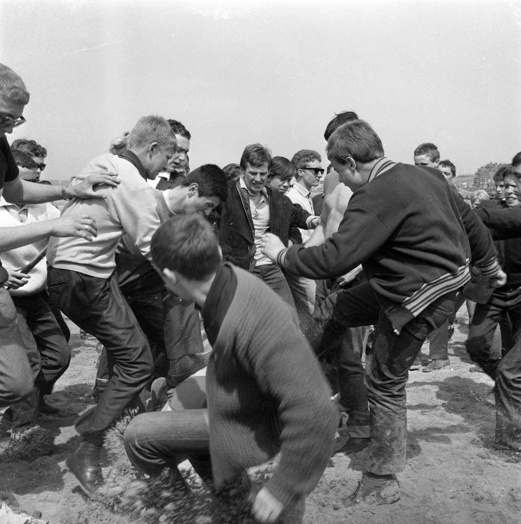 A youth lying on the sand at Margate, Kent, May 18, 1964, is the centre of a fight which broke out when Mods and Rockers clashed on the beach at the seaside resort. Police arrested many of the youths. (AP Photo) Ref #: PA.8634315