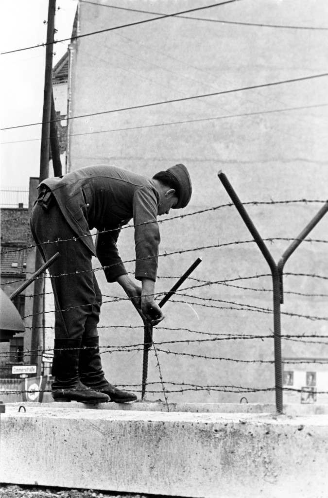 An East Berlin soldier secures a steel bar to hold the barbed wire atop the Berlin Wall on sector border in Berlin near Friedrichstrasse in Germany on Sept. 30, 1961. The Communists are tightening border security as a result of repeated escapes in this area to the West by East Germans. (AP Photo) PA-8635257