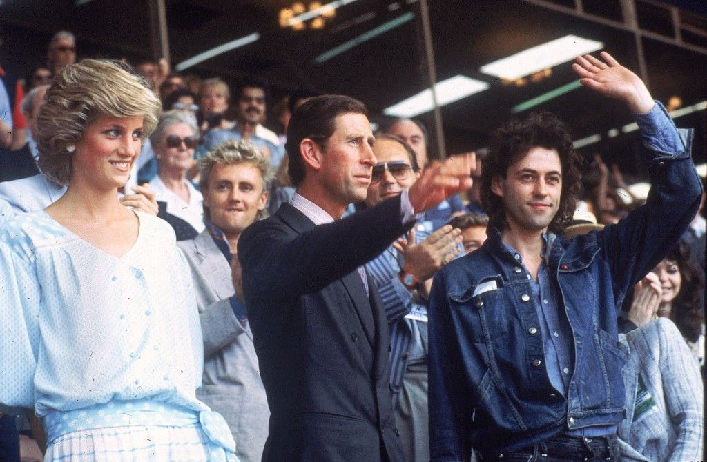 Princess Diana, left, and Prince Charles attend the Live Aid concert as they acknowledge the crowd with event organizer Bob Geldof, right, at London's Wembley Stadium, England, July 13, 1985. The rock and roll telethon concert, to raise awareness for famine victims in Ethiopia, was broadcast around the world and raised $100 million dollars. (AP Photo/Joe Schaber)  PA-8636492