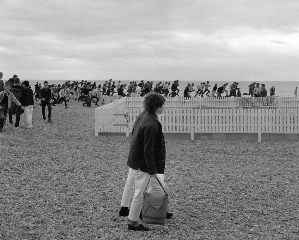 Passersby watch Mods surge along the beach at Hastings, Sussex, Aug. 2, 1964, in search of bank holiday entertainment. A squad of policemen were flown in from Middlesex after sporadic outbreaks of trouble between rival gangs. (AP Photo/Frank Leonard Tewkesbury) Ref #: PA.8642623  Date: 02/08/1964