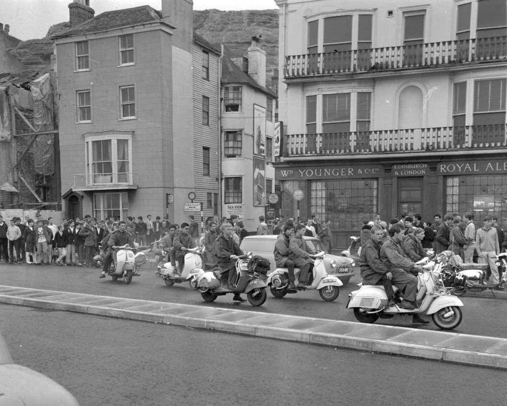 Mods on scooters drive two-by-two through Hastings, Sussex, Aug. 2, 1964, as teenagers converge on the resort in search of bank holiday entertainment. A squad of policemen were flown in from Middlesex after sporadic outbreaks of trouble between rival gangs. (AP Photo/Frank Leonard Tewkesbury) Ref #: PA.8643145