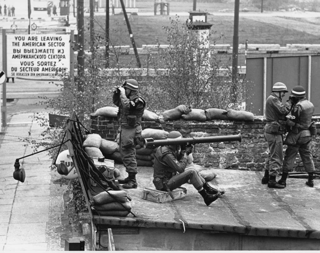 A bazooka squad of U.S. Military Police man a rooftop position on Oct. 29 1961, near the Friedrich Strasse border. The position is atop a hut some 200 yards from East German border guards, seen beyond sign indicating edge of American sector in West Berlin. (AP Photo) Ref #: PA.8646525 Date: 29/10/1961