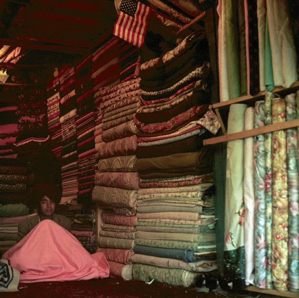 A shopkeeper is shown in a cloth shop where a small American flag is displayed among the rows of folded fabric in the old quarter of Kabul, capital city of Afghanistan - 1960