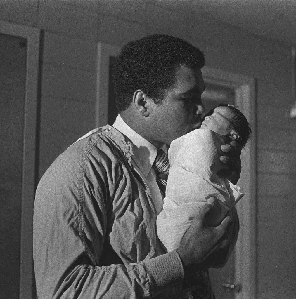 Heavyweight champion Muhammad Ali gives a kiss to his new-born daughter. The 7-pound, 10-ounce infant was born Dec. 30, 1977 in Miami Beach, Fla. The baby is Ali's fifth daughter. (AP Photo) Ref #: PA.8649614  Date: 30/12/1977