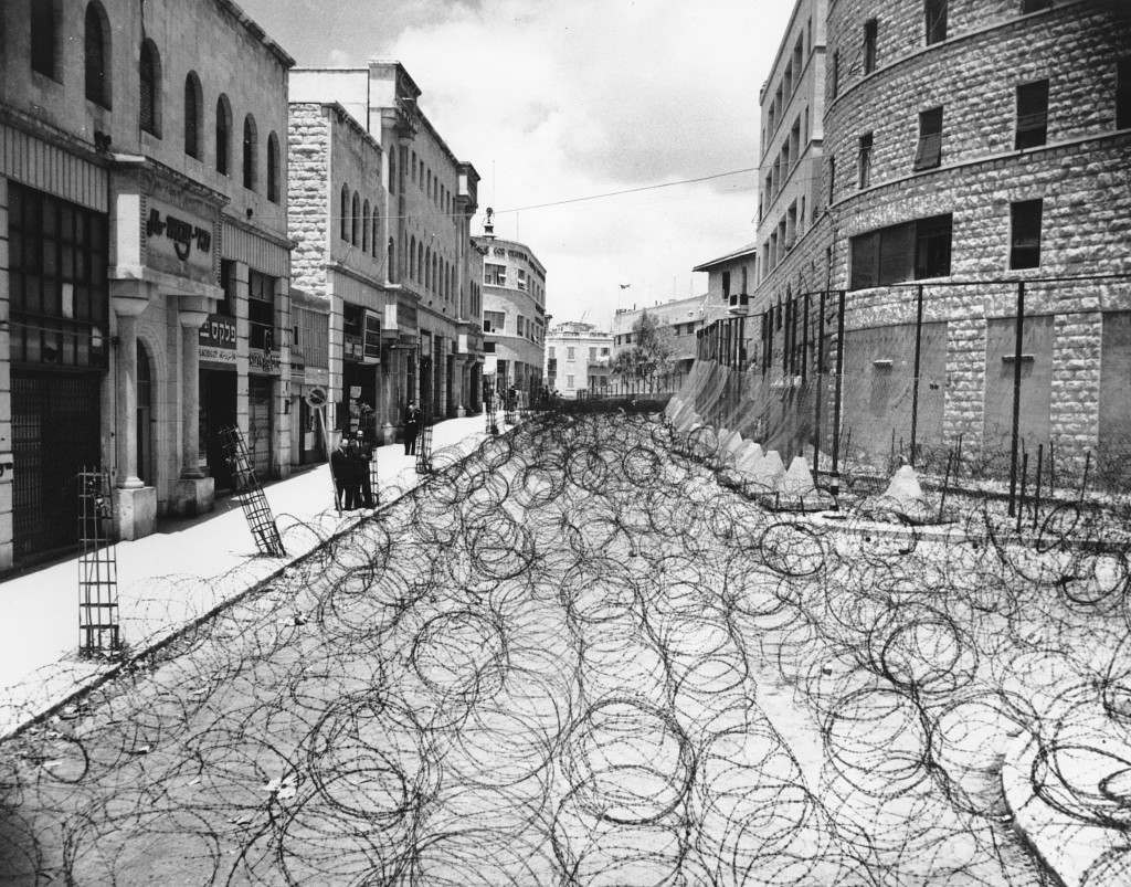 Barbed wire covers the entire roadway for 105 yards on Princess Mary Ave. in Jerusalem at Zion Square on May 19, 1948. The wire is meant to keep Arabs and Jews from coming in contact. The Jewish State of Israel was proclaimed on May 15, and Britain was forced to surrender its 25-year mandate. On this day, the Old City of Jerusalem appeared in imminent danger of being wrested from its Jewish defenders by Palestine's King Abdullah's desert legion. In the background is the Jewish section. Right at center is the police headquarters. (AP Photo) Ref #: PA.8650556 Date: 19/05/1948