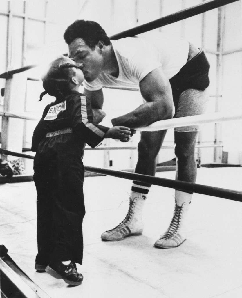 Former world boxing champion George Foreman gets a big kiss from his 3-year-old daughter Mitchy as she visits him at the gym on his farm in Marshall, Texas, on June 11, 1976. Foreman is preparing for his June 15 bout against Joe Frazier in New York. (AP Photo) Ref #: PA.8652427  Date: 11/06/1976