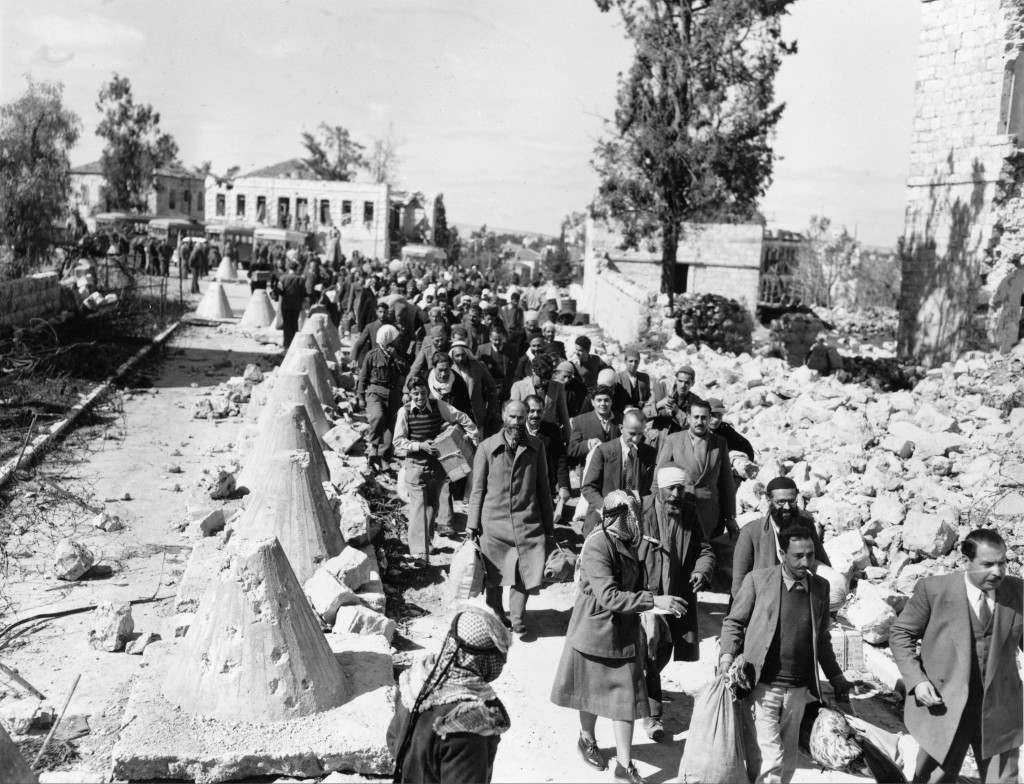 Arab civilians, released by Jews under a prisoner exchange agreement, walk through a debris-flanked no-mans-land road as they return to Arab territory in Jerusalem, March 8, 1949. The Israel-Jordan Armistice Agreement provided for the exchange of Arab civilian prisoners and about 800 Jewish prisoners of war. (AP Photo/Ali Hassan Abu Zarur) Ref #: PA.8658443 Date: 08/03/1949