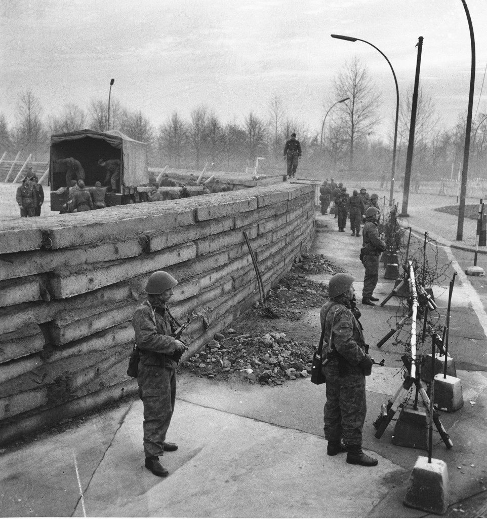 West Berlin police stand guard behind barbed wire along the new 250-yard massive concrete wall at Berlin's Brandenburg Gate, Germany, on Nov. 23, 1961. Beyond the wall Communists pull down fibre board screen behind which building of operations took place. The material used for the screen can be seen loaded into the truck on other side of the concrete barrier. (AP Photo)PA-8661390