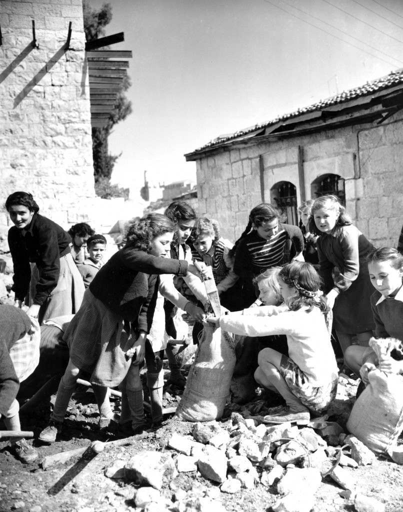 Sandbags for defense works are filled by Jewish girls in the Montefiore quarter of Jerusalem in Feb. 1948. The girls belong to the few Jewish families still remaining in the section with members of the Haganah, Defense Organization. This section has been under constant attack by Arab snipers from the Old City during Arab-Jewish conflict after United Nations decision to partition Palestine. (AP Photo/James Pringle) Ref #: PA.8666931 Date: 01/02/1948