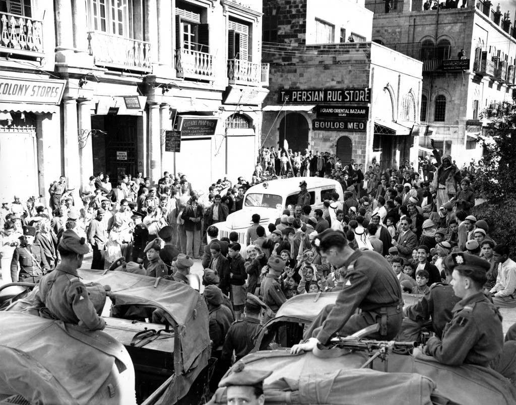 A white Jewish ambulance, with a British soldier riding aboard, carries wounded Jews through a crowd of Arabs at Jaffa Gate in Jerusalem as British soldiers keep watch in Dec. 1947. The Arabs, who were imprisoned inside Jerusalem's Old City during curfew hours, did not attack the ambulance. (AP Photo/James Pringle) Ref #: PA.8669141 Date: 01/12/1947