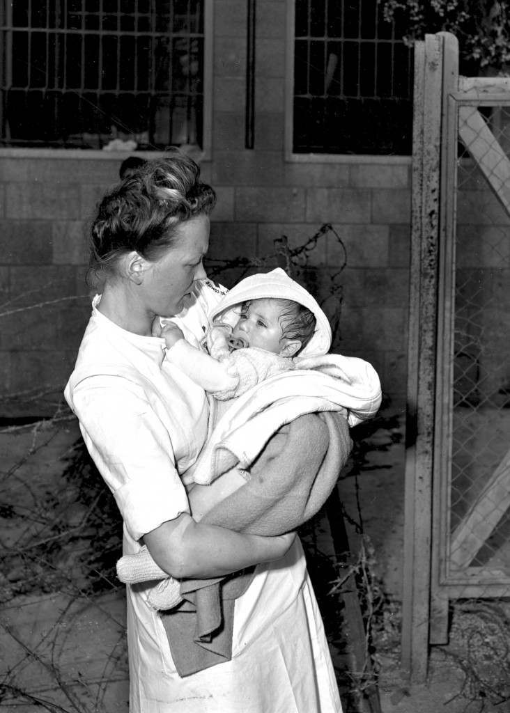 A Red Cross nurse holds a young baby being repatriated from the Haganah-held sector of Jerusalem to the Arab section on June 18, 1948 during the Arab-Israeli War. The child is one of many Arab children, women and men found among the ruins of the city by Jewish forces. Refugees are met at the New Gate by representatives of the International Red Cross, supervising the transfer. (AP Photo) Ref #: PA.8672022 Date: 18/06/1948