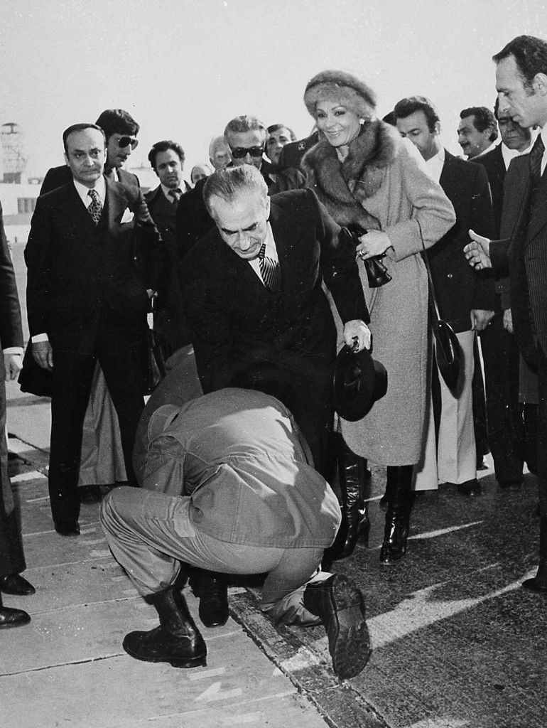 A soldier bends to kiss the feet of Shah Mohammad Reza Pahlavi on the tarmac of Tehran's Mehrabad Airport, in this Jan. 16, 1979 photo. Behind the Shah is his wife Empress Farah. Others are not identified. (AP Photo) Ref #: PA.8684909  Date: 17/01/1979