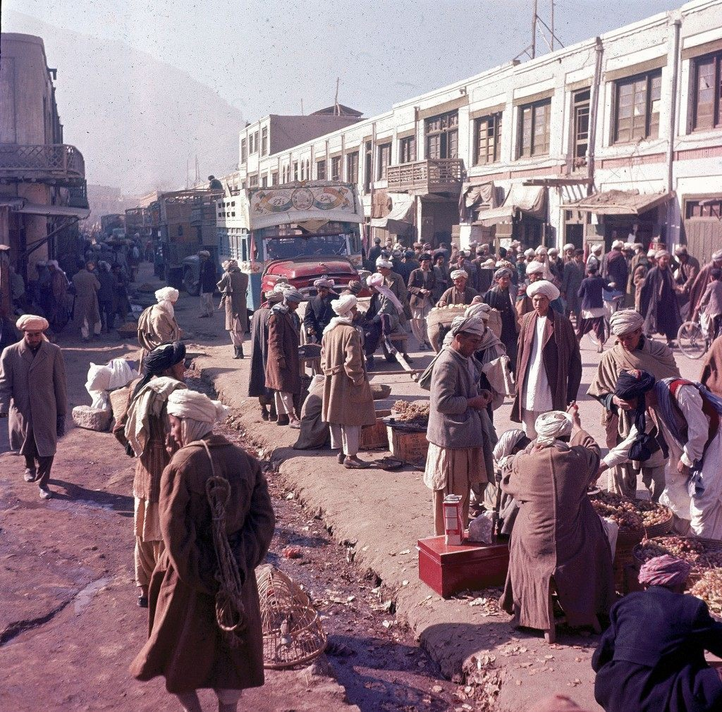 TThis general view shows roadside vendors and men strolling as a painted truck makes its way through the busy street in Kabul, Afghanistan, Nov. 1961. (AP Photo/Henry S. Bradsher) Ref #: PA.8689944 Date: 01/11/1961