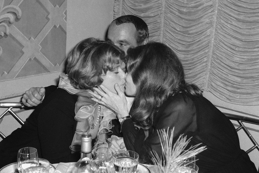 "Faye Dunaway, right, and Maria Schell kiss as movie director Stuart Rosenberg, hidden in back, looks on at a dinner-dance at the St. Regis Hotel in New York, Dec. 19, 1976. The dinner preceded the premiere of the movie ""Voyage of the Damned,"" directed by Rosenberg and starring an international array of stars including Dunaway and Schell. (AP Photo) Ref #: PA.8698680  Date: 19/12/1976"