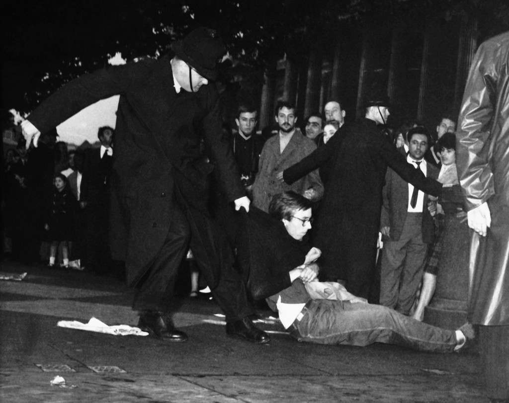 A young man in Beatnik style clothes is dragged along by a policeman a another holds back a section of the crowd during the ban he home rally in London's Trafalgar Square, United Kingdom on Sept. 17, 1961. Extra police were on duty on handle the huge crowd, estimated at over 10,000 which gathered in the square. Several skirmishes took place and at 6.15 pm 86 people had been arrested. (AP Photo) Ref #: PA.8792989